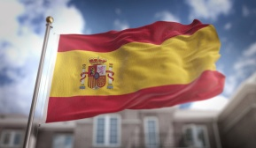 Spain Flag 3D Rendering on Blue Sky Building Background